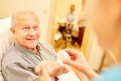 caregiver offering senior man a medication