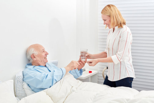 caregiver offering senior man a glass of water